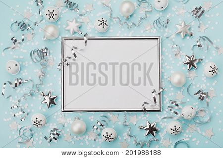 Party carnival christmas background decorated silver frame with confetti balls and star on turquoise desk top view. Flat lay. Holiday mockup invitation. Greeting card with copy space.