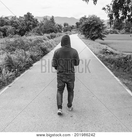 The silhouette of man Walking alone on the road concept of lonely sad alone person space alone and scared