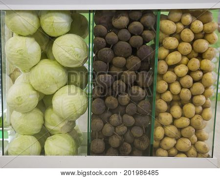 Vegetables in supermarket - turnips, potato and cabbage at grocery store, close up