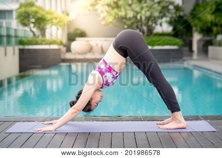 Beautiful young Asian woman doing yoga exercise with downward facing dog posing (Adho Mukha Svanasana) near swimming pool. Healthy lifestyle and good wellness concepts