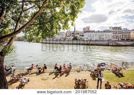 PARIS, FRANCE - August 07, 2017: People resting on the riverside cafe near the Arcole bridge in Paris