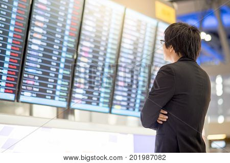 Young asian business man checking his flight from the flight information at airport terminal