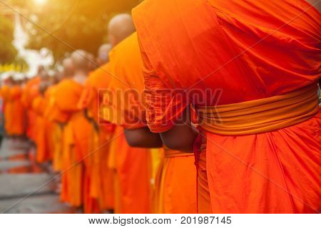 Buddhist philanthropy concept. Buddhist Monks line up in row waiting for Buddhism people to give alms bowl in Thai temple at morning time. Selective focus at front Monk. Light with len flare effect