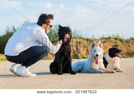 young man kneeling beside three dogs outdoor