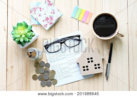 Business, finance, saving money, banking, property loan or mortgage concept : Top view or flat lay of saving account book or financial statement, wood house model and coins on office desk table