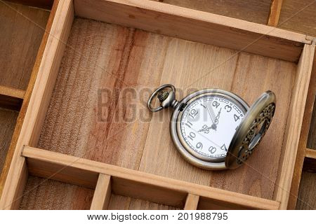 old pocket watch in old wooden container