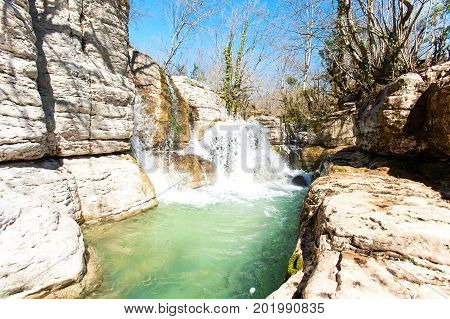 Spectacular waterfalls in woodland of Okatse canyon Georgia. Colorful vibrant outdoors vertical image.