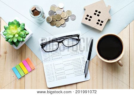 Business, finance, savings, property ladder, mortgage loan concept : Top view or flat lay of saving account passbook or financial statement, wood house model, and accessories on wooden background