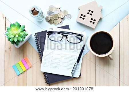Business, finance, property ladder or mortgage loan concept : Top view or flat lay of saving account passbook or financial statement, wood house model, and coins on office desk table