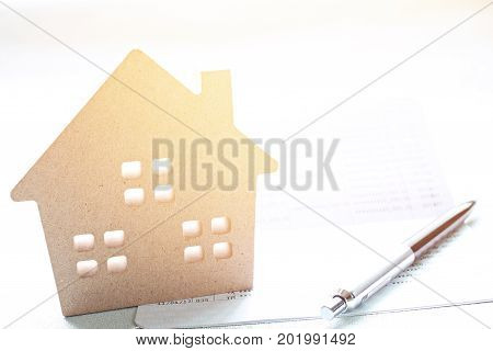 Business, finance, savings, property ladder or mortgage loan concept : Wood house model and pen on saving account passbook  or financial statement