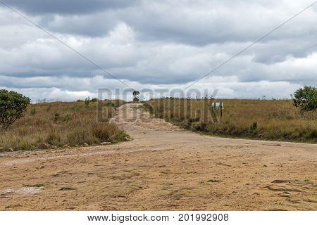 Empty Rural Dirt Road Leading Through Dry Winter Grassland