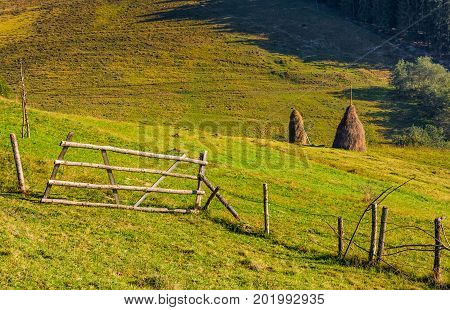 Hay Stacks Behind The Fence On Rural Field