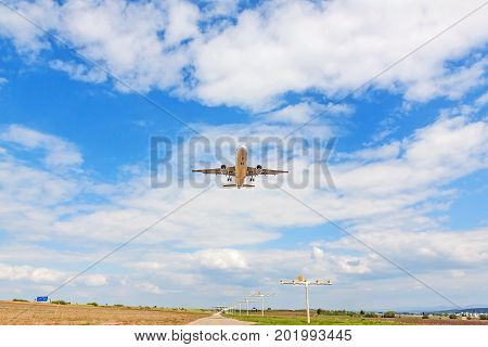 Flying airplane from below - landing approach - blue sky with clouds