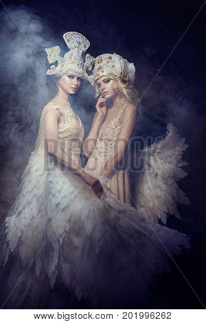 Angel nymph fairy art pictures of women. Girls with angel wings beauty models posing on a dark background. Fairy tale magic magical girl in gorgeous expensive dresses