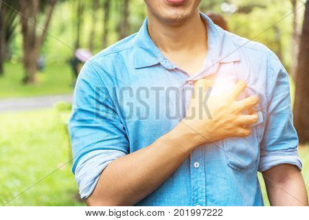 Elderly man holding hands on chest suffering from heart attack closeup