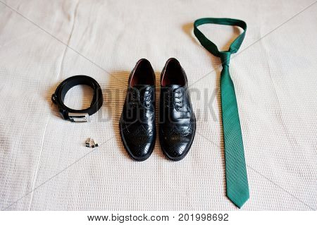 Close-up Photo Of Groom's Black Shoes, Belt, Golden Cufflinks And Green Tie.