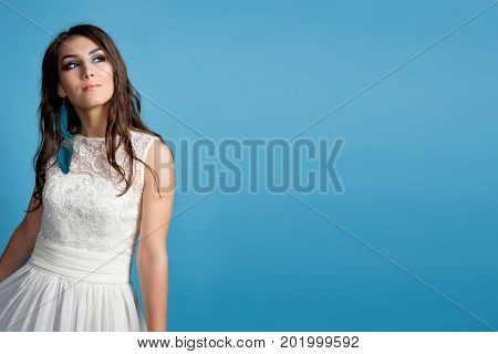 bride dreaming blue background. Brunette young pretty woman in white dress is dreaming. Desire. Copy space