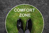 Businessman standing on green and gray carpet with comfort zone text on it poster