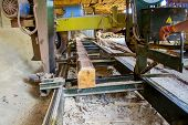 Sawmill. Process of machining logs in equipment sawmill machine saw saws the tree trunk on the plank boards. Wood sawdust work sawing timber wood wooden woodworking poster