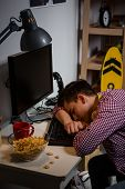 Teenage boy tired falling asleep at computer table. Problem of modern teenagers using computers too much. poster