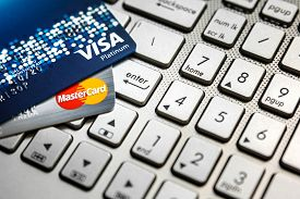 Bangkok Thailand - August 24 2017: Close up shot of 2 credit cards VISA and Mastercard on laptop computer with enter button focusing.