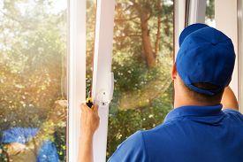 worker in blue uniform installing new plastic pvc window
