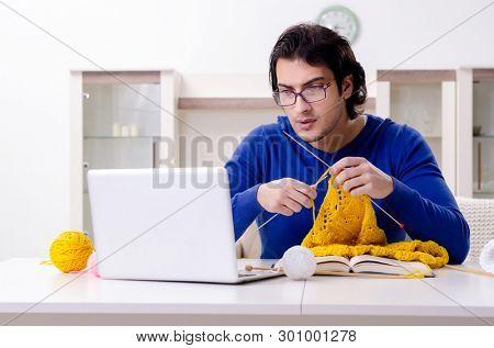 Young good looking man knitting at home