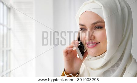 Portrait Of Attractive Muslim Woman In White Hijab Is Talking Mobile Phone And Smilng Standing Near