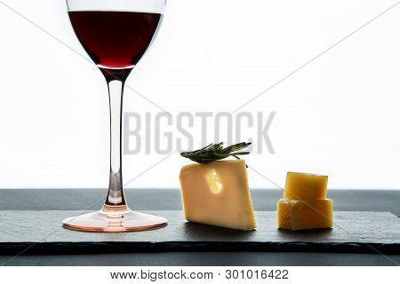 Glass Of Red Wine Garnished With Grape And Pieces Of Savory Hard Cheese