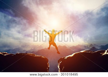 Man jumping for joy between two mountains at sunset. Concept of challenge, taking a risk, having fun. 3d illustration
