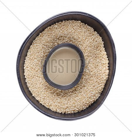 Tahini Sauce And Sesame Seeds In Black Bowls Isolated On White Background. Natural Paste Made From S