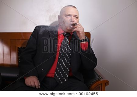 Aged serious business man in suit smoking cigar on leather sofa in smoked-up office. Focus on cigar