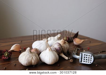 Garlic, garlic cloves and spices on a wooden table. Exquisite seasoning. Natural flavor. Antibacterial, boosts immunity. The concept of healthy organic food, alternative medicine poster