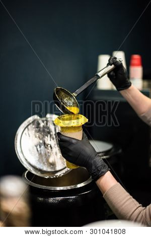 Young Lady Kitchen Worker Pours Soup Into Cup