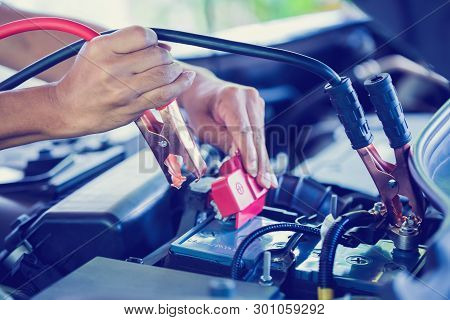 selective focus charging car with electricity trough cables. first connect anode then follow connect negative connector battery poster