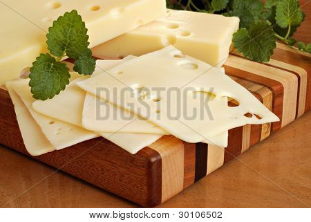 Still life image of swiss cheese on wooden butcher block cutting board with herbs.  Macro with shallow dof.