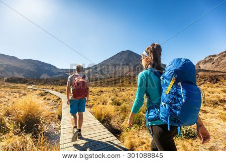 New Zealand Hiking Couple Backpackers Tramping At Tongariro National Park. Male and female hikers hiking by Mount Ngauruhoe. People living healthy active lifestyle outdoors