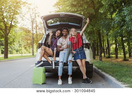 Happy Friends Sitting In Open Car Back With Salutation Gesture. Millennials Traveling Concept