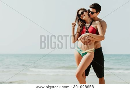 Portrait Of Romantic Young Beautiful Couple In Love Embracing At The Beach. Couple On Travel Honeymo