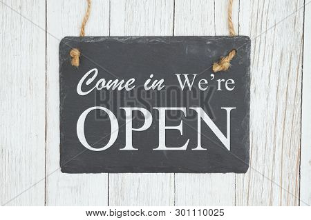 Come In We're Open Text On A Hanging Chalkboard On Weathered Whitewash Textured Wood