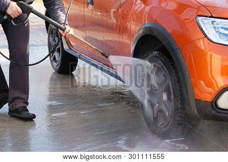 Man Washes His Orange Car At Car Wash. Cleaning With Water At Self-service Car Wash. Soapy Water Run
