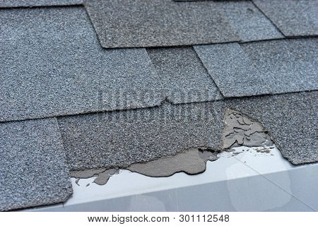 Сloseup View Of Asphalt Shingles Roof Damage That Needs Repair.