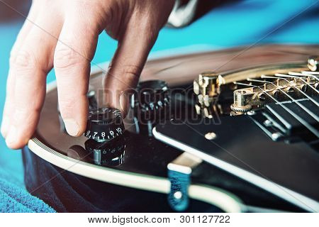 Male Hand Changing Electric Guitar Settings. Tuning A Timbre Regulator