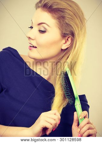 Woman brushing her long blonde hair using brush, morning beauty routine. Haircare and hairstyling concept. poster