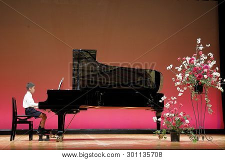 Japanese Boy Playing Piano On Stage (fourth Grade At Elementary School)