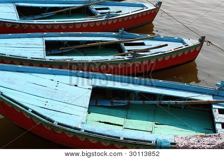 Colorful boats on brown waters of Ganges river Varanasi India poster