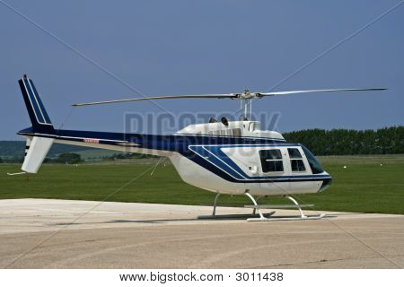 Side Of White Helicopter Parked At Airport