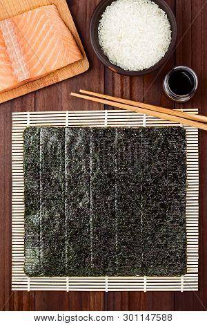 Sushi Ingredients, Nori Seaweed On Makisu Bamboo Mat For Rolling,  Fresh Raw Salmon, Raw Sushi Rice,