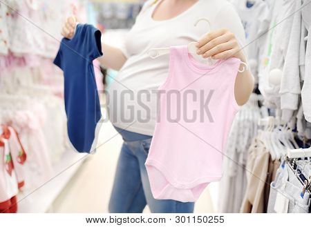Young Pregnant Woman Choosing Pink Or Blue Clothes In The Store For Newborns. Shopping For Expectant
