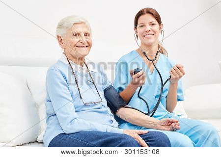 Young nurse and senior woman as a patient in blood pressure measurement